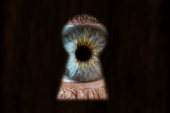 Female Blue Eye Looking Through The Keyhole. Concept Of Voyeuris