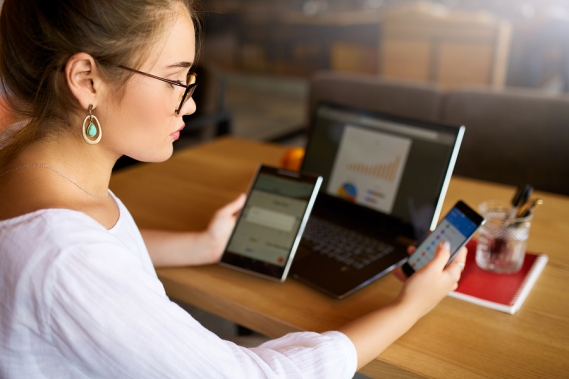 Mixed Race Woman In Glasses Working With Multiple Electronic Int